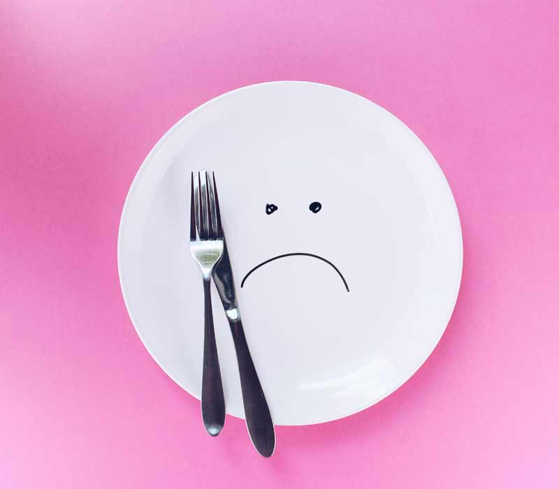 white dinner plate with sad face drawn on it