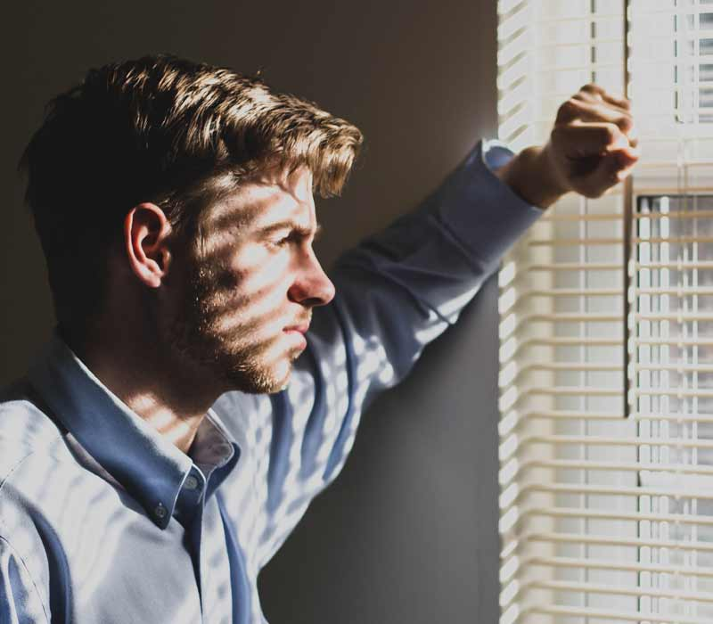 Man looking out the window concerned