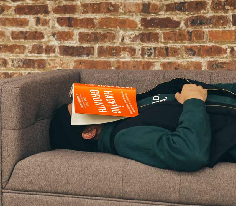 man sleeping with book on his face