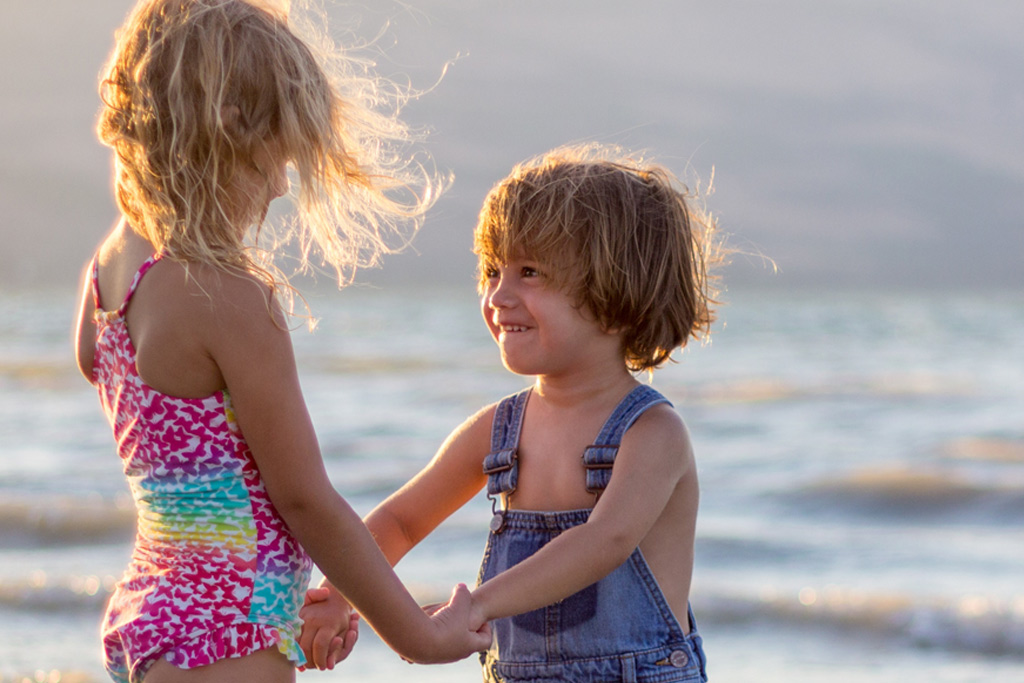 Two young children holding hands at the beach smiling at each other. PANS & PANDAS Clinic