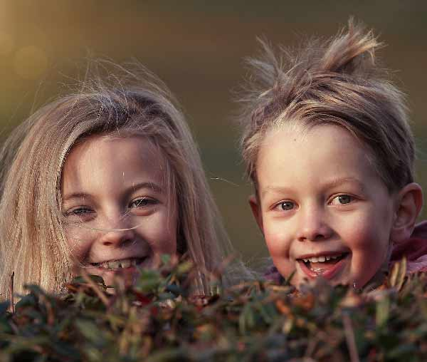 two happy young children smiling over a hedge