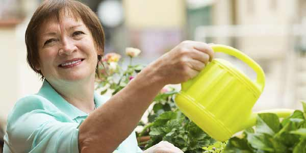 Happy woman watering her plants