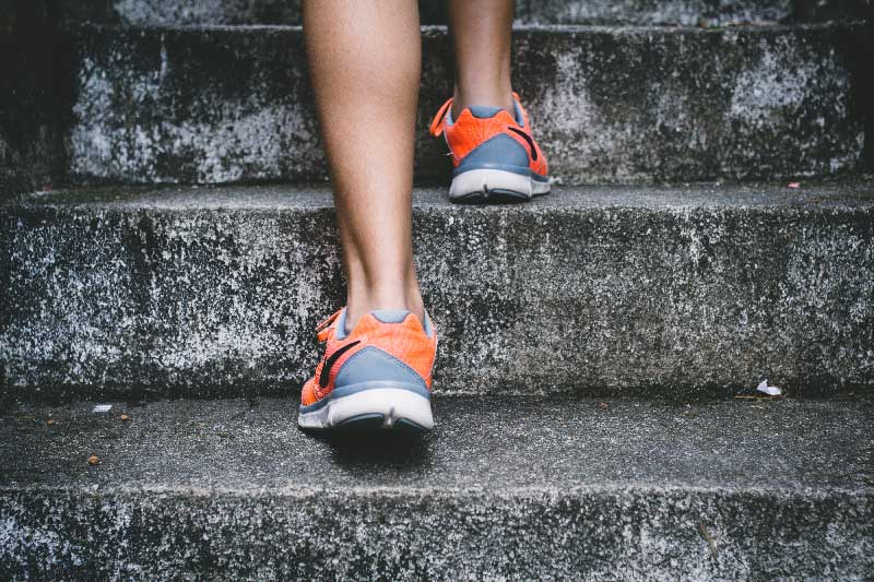 a woman's running shoes going up stairs