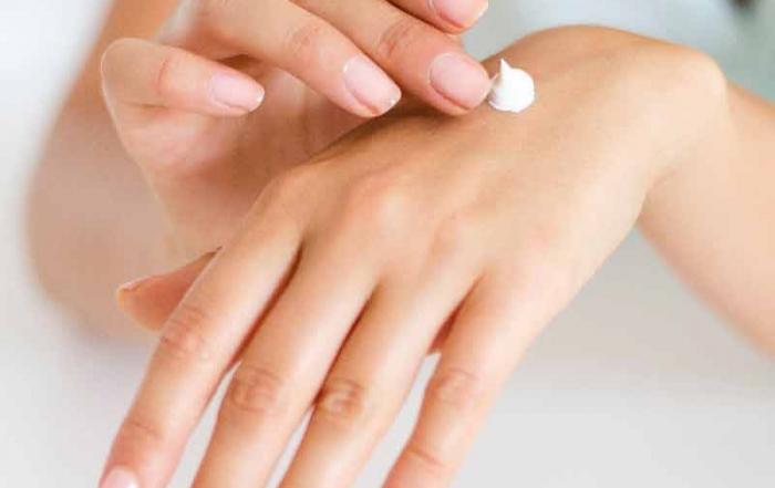 a woman applying hand lotion