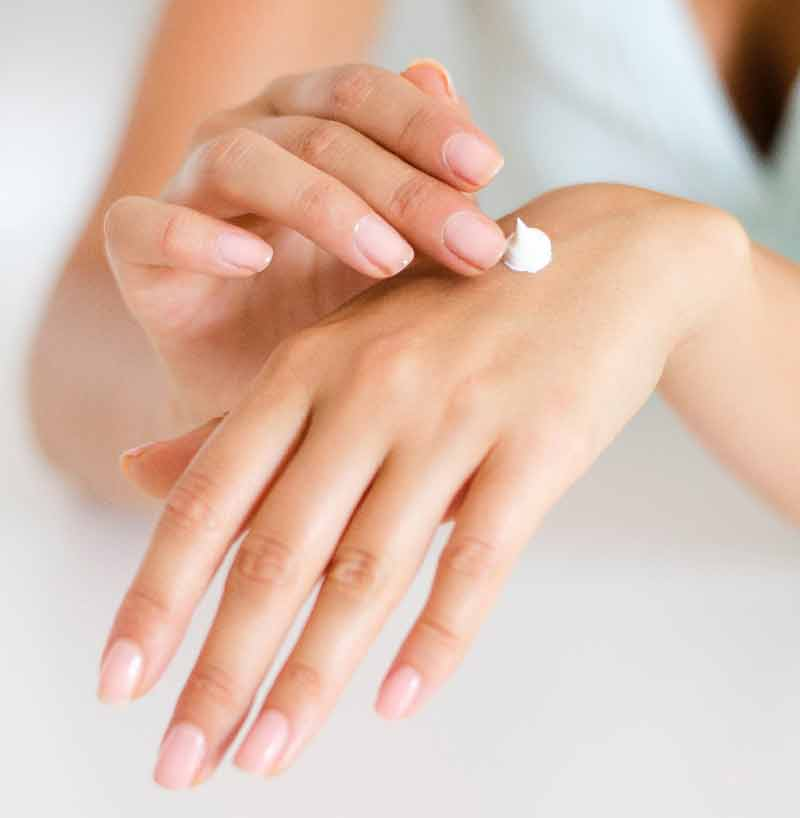 a woman applying hand lotion
